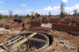 Väggarna på Hus A växer till sig och grunden för vattentankens takbygge läggs samtidigt som en leverans av tegel lastas av.