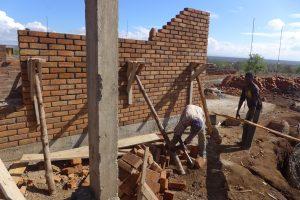 De övre lagren med tegel läggs för Hus C. Byggnadsställningarna skiljer sig från de hemma, här sätts stora hyllfästen upp på väggen som endast hålls på plats av vinklade pålar som bankas ner i marken. Sedan läggs plankor på att stå på.