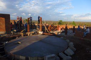 Snart skymning och de sista stenarna för dagen läggs på pelarna. I förgrunden syns den färdiga vattentanken.